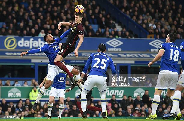 TOPSHOT Manchester City's English defender John Stones jumps for the ball against Everton's Englishborn Welsh defender Ashley Williams during the...