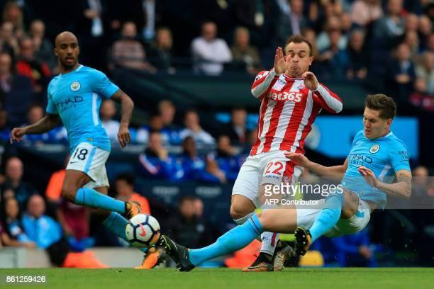 Manchester City's English defender John Stones tackles Stoke City's Swiss forward Xherdan Shaqiri during the English Premier League football match...