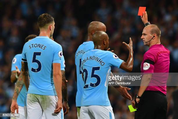 Manchester City's English defender Kyle Walker is shown the red card by referee Robert Madley as Manchester City's English defender John Stones and...