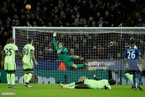 Manchester City's English goalkeeper Joe Hart dives as a shot from Leicester City's Algerian midfielder Riyad Mahrez goes over during the English...