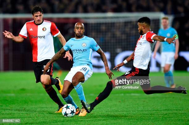 Manchester City's English midfielder Fabian Delph vies for the ball with Feyenoord's Dutch defender Eric Botteghin and Feyenoord's Dutch defender...