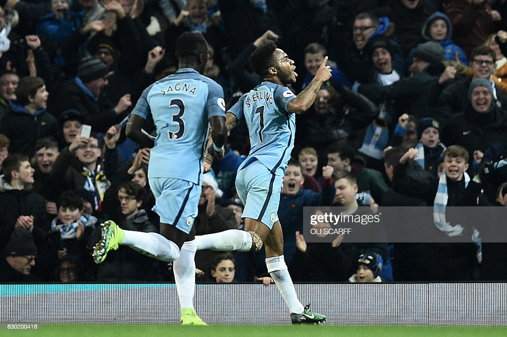Manchester City's English midfielder Raheem Sterling (R) celebrates scoring his team's second goal during the English Premier League football match between Manchester City and Arsenal at the Etihad Stadium in Manchester, north west England, on December 18, 2016. / AFP / Oli SCARFF / RESTRICTED TO EDITORIAL USE. No use with unauthorized audio, video, data, fixture lists, club/league logos or 'live' services. Online in-match use limited to 75 images, no video emulation. No use in betting, games or single club/league/player publications. /