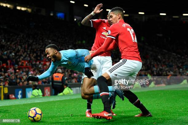 Manchester City's English midfielder Raheem Sterling goes down as Manchester United's English defender Chris Smalling challenges during the English...