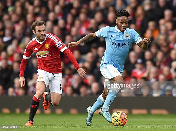 Manchester City's English midfielder Raheem Sterling is challenged by Manchester United's Spanish midfielder Juan Mata during the English Premier...