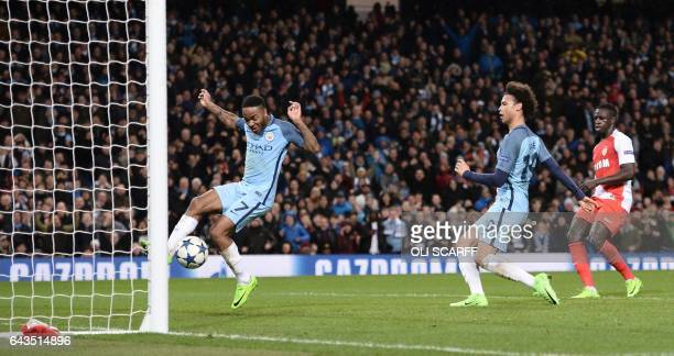 Manchester City's English midfielder Raheem Sterling jumps out of the way as Manchester City's German midfielder Leroy Sane taps in their fifth goal...