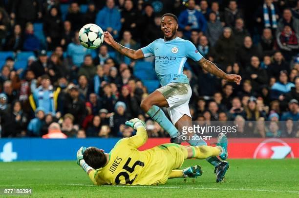 TOPSHOT Manchester City's English midfielder Raheem Sterling lifts the ball over Feyenoord's Australian goalkeeper Brad jones to score the opening...