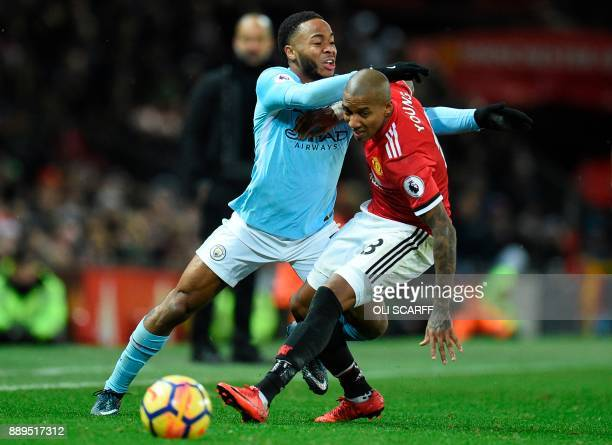 Manchester City's English midfielder Raheem Sterling tangles with Manchester United's English midfielder Ashley Young during the English Premier...