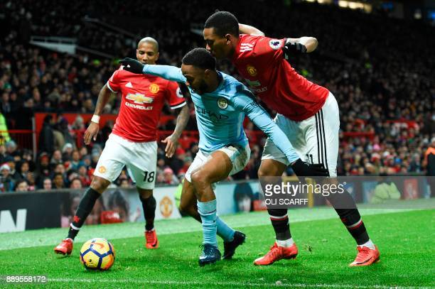 Manchester City's English midfielder Raheem Sterling tries to shield the ball from Manchester United's French striker Anthony Martial during the...