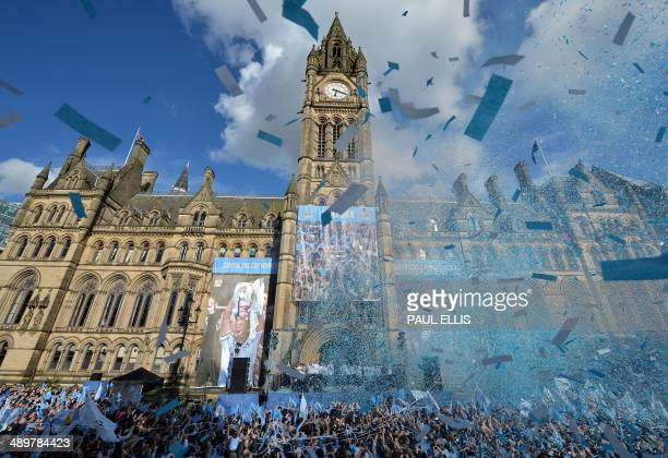 Manchester City's footballers celebrate outside Manchester Town Hall as they prepare to take part in a victory parade on an opentopped bus through...