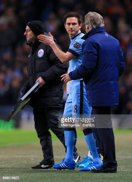 Manchester City's Frank Lampard speaks with Manchester City manager Manuel Pellegrini before being substituted on