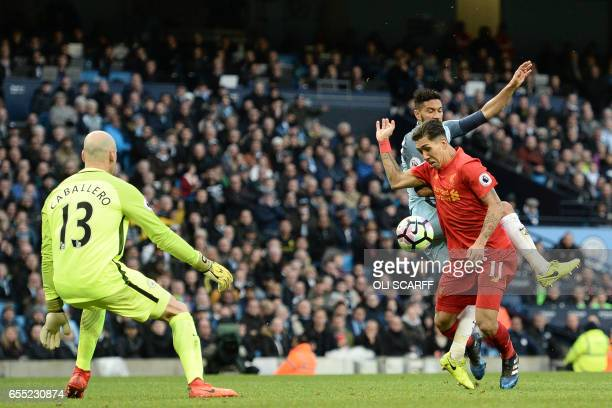 Manchester City's French defender Gael Clichy fouls Liverpool's Brazilian midfielder Roberto Firmino to give away a penalty during the English...
