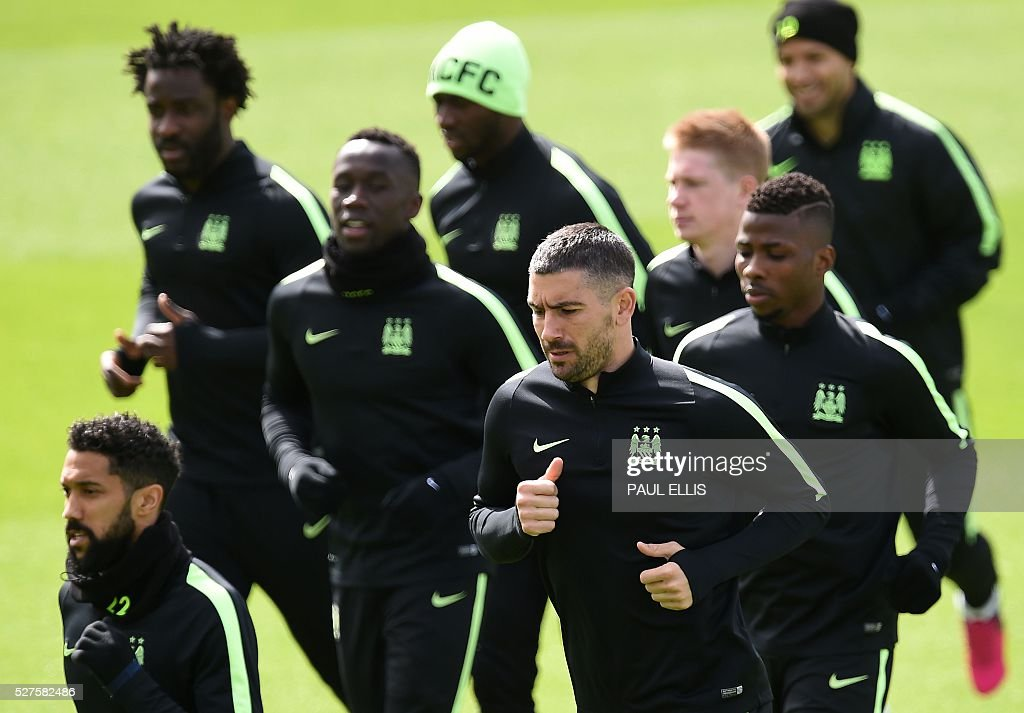 Manchester City's French defender Gael Clichy (L), Manchester City's Serbian defender Aleksandar Kolarov (C) and Manchester City's Nigerian striker Kelechi Iheanacho (R) warm up during a team training session at the City Academy in Manchester, north west England, on May 3, 2016. Manchester City will play against Real Madrid CF in a UEFA Champions League semi-final second leg football match in Madrid on May 4. / AFP / PAUL