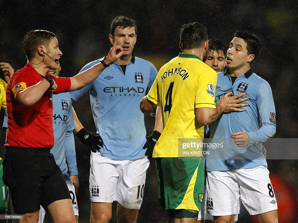 """Manchester City's French midfielder Samir Nasri (R) is sent off by referee Mike Jones (L) after confronting Norwich City's Cameroonian defender Sebastien Bassong during the English Premier League football match between Norwich City and Manchester City at Carrow Road stadium in Norwich, England on December 29, 2012. USE. No use with unauthorized audio, video, data, fixture lists, club/league logos or """"live"""" services. Online in-match use limited to 45 images, no video emulation. No use in betting, games or single club/league/player publications."""