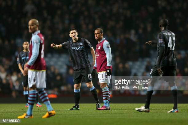Manchester City's Gareth Barry speaks with teammate Yaya Toure as Aston Villa's Gabriel Agbonlahor looks on