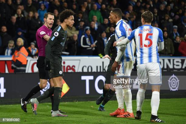 Manchester City's German midfielder Leroy Sane and Huddersfield Town's Dutch midfielder Rajiv van La Parra clash at the end of the English Premier...