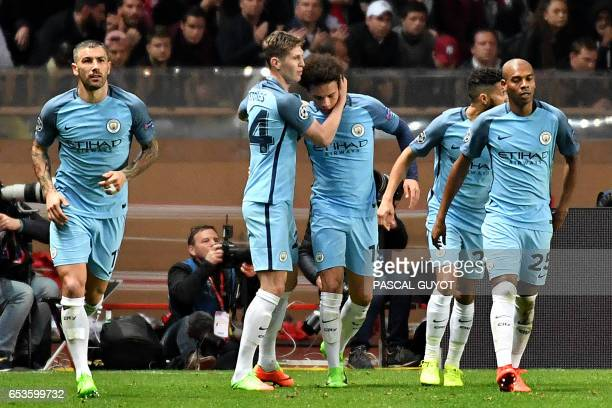 Manchester City's German midfielder Leroy Sane celebrates with teammates after scoring a goal during the UEFA Champions League round of 16 football...