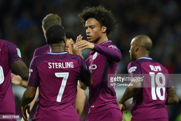 Manchester City's German midfielder Leroy Sane celebrates with teammates after scoring the opening goal of the English League Cup third round...