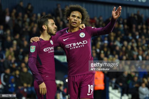 Manchester City's German midfielder Leroy Sane celebrates with Manchester City's Portuguese midfielder Bernardo Silva after scoring their second goal...