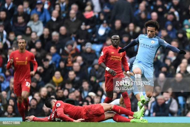 Manchester City's German midfielder Leroy Sane is tackled by Liverpool's German midfielder Emre Can during the English Premier League football match...