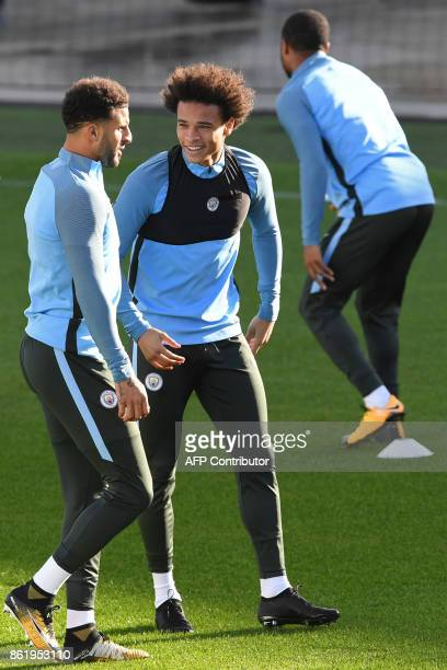 Manchester City's German midfielder Leroy Sane talks with Manchester City's English defender Kyle Walker during a team training session at the City...
