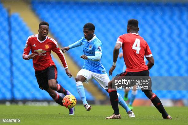 Manchester City's Isaac BuckleyRicketts takes on Manchester United's Timothy FosuMensah and Matty Willock
