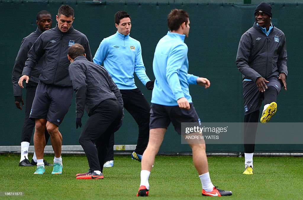 Manchester City's Italian forward Mario Balotelli (R) attends a team training session with Manchester City's English midfielder James Milner (2R) Manchester City's French midfielder Samir Nasri (3R) at the Carrington training complex, in Manchester, north-west England on November 20, 2012, on the eve of their UEFA Champions League football match against Real Madrid in Manchester. AFP PHOTO / ANDREW YATES