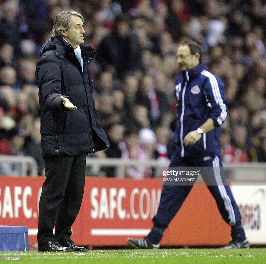"""Manchester City's Italian manager Roberto Mancini (L) gestures and Sunderland's Northern Irish manager Martin O'Neill (R) walks back from the touch line during the English Premier League football match between Sunderland and Manchester City at The Stadium of Light in Sunderland, north-east England on December 26, 2012. USE. No use with unauthorized audio, video, data, fixture lists, club/league logos or """"live"""" services. Online in-match use limited to 45 images, no video emulation. No use in betting, games or single club/league/player publications."""