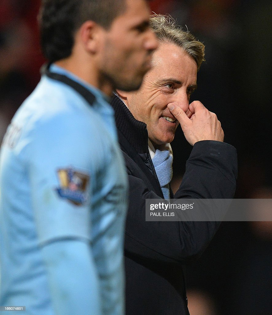 "Manchester City's Italian manager Roberto Mancini (R) gestures as he leaves the pitch after his team's victory in the English Premier League football match between Manchester United and Manchester City at Old Trafford in Manchester, northwest England on April 8, 2013. Manchester City won the game 2-1. USE. No use with unauthorized audio, video, data, fixture lists, club/league logos or ""live"" services. Online in-match use limited to 45 images, no video emulation. No use in betting, games or single club/league/player publications."