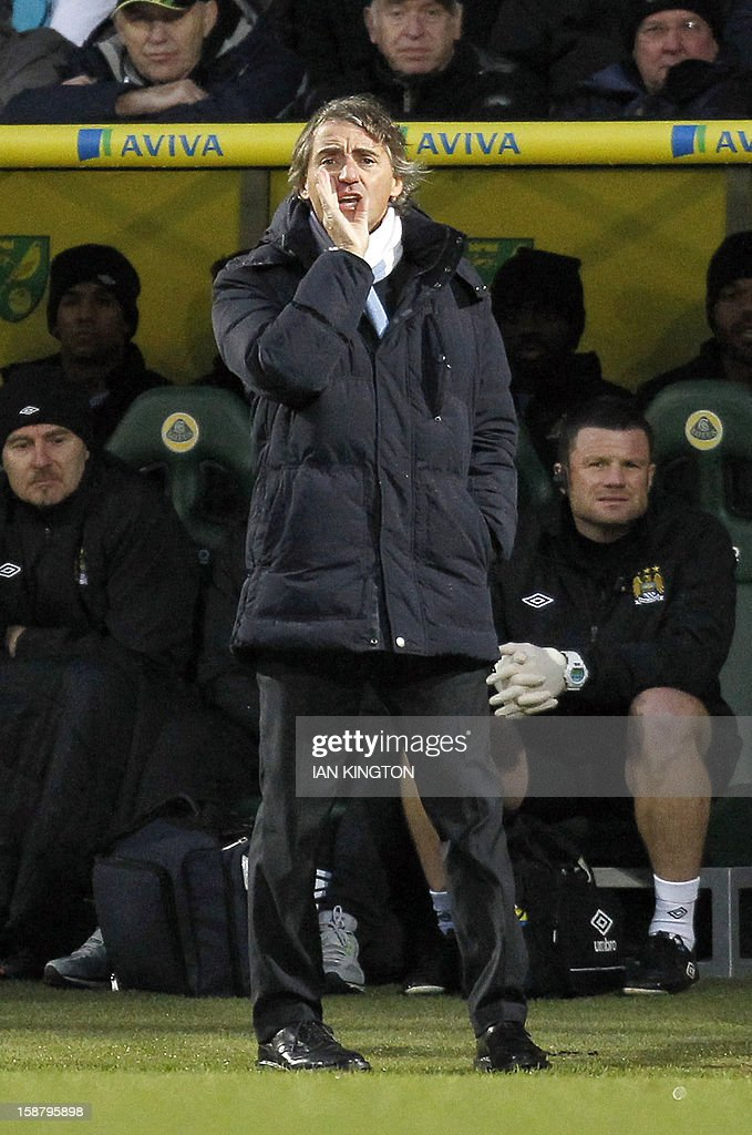"""Manchester City's Italian manager Roberto Mancini shots instructions to his players during the English Premier League football match between Norwich City and Manchester City at Carrow Road stadium in Norwich, England on December 29, 2012. USE. No use with unauthorized audio, video, data, fixture lists, club/league logos or """"live"""" services. Online in-match use limited to 45 images, no video emulation. No use in betting, games or single club/league/player publications."""