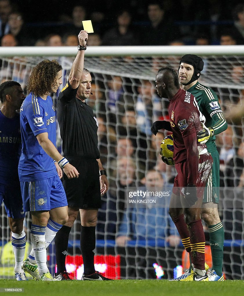 """Manchester City's Italian striker Mario Balotelli (2nd R) is given the yellow card by referee Chris Foy during an English Premier League football match between Chelsea and Manchester City at Stamford Bridge stadium in London on November 25, 2012. USE. No use with unauthorized audio, video, data, fixture lists, club/league logos or """"live"""" services. Online in-match use limited to 45 images, no video emulation. No use in betting, games or single club/league/player publications"""