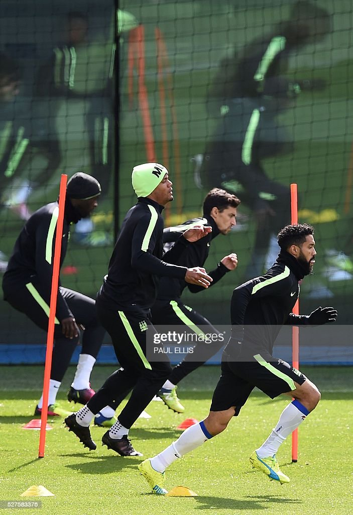 Manchester City's Ivorian midfielder and captain Yaya Toure (L), Manchester City's Belgian defender Vincent Kompany (2L), Manchester City's Spanish midfielder Jesus Navas (2R) and Manchester City's French defender Gael Clichy attend a team training session at the City Academy in Manchester, north west England, on May 3, 2016. Manchester City will play against Real Madrid CF in a UEFA Champions League semi-final second leg football match in Madrid on May 4. / AFP / PAUL