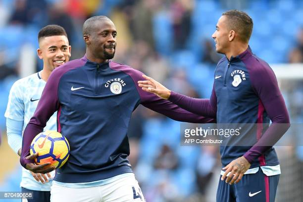 Manchester City's Ivorian midfielder Yaya Toure and Manchester City's Brazilian defender Danilo chat as they warm up ahead of the English Premier...