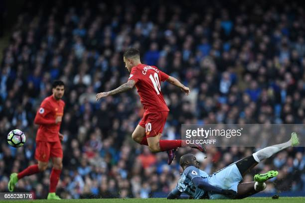 Manchester City's Ivorian midfielder Yaya Toure attempts a tackle on Liverpool's Brazilian midfielder Philippe Coutinho during the English Premier...