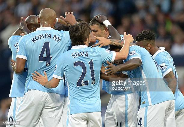 Manchester City's Ivorian midfielder Yaya Toure celebrates with teammates after scoring from a deflection during the English Premier League football...