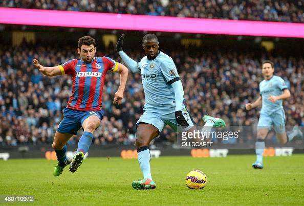 Manchester City's Ivorian midfielder Yaya Toure shoots to score their third goal as Crystal Palace's Australian midfielder Mile Jedinak closes in...