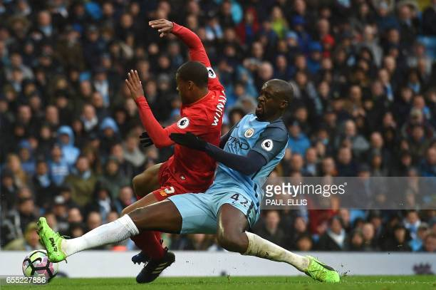 Manchester City's Ivorian midfielder Yaya Toure tackles Liverpool's Dutch midfielder Georginio Wijnaldum during the English Premier League football...