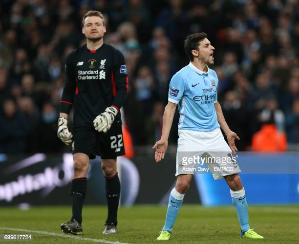 Manchester City's Jesus Navas celebrates scoring in the penalty shoot out as Liverpool goalkeeper Simon Mignolet appears dejected