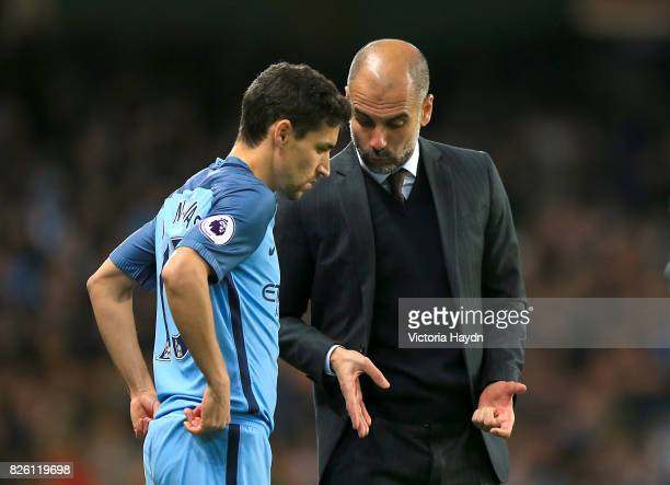 Manchester City's Jesus Navas speaks with Manchester City manager Pep Guardiola