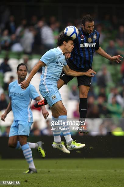 Manchester City's Karim Rekik and Inter Milan's Giampaolo Pazzini battle for a ball in the air