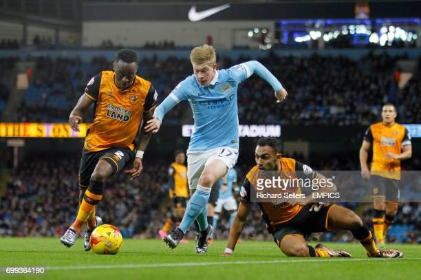 Manchester City's Kevin De Bruyne gets past Hull City's Moses Odubajo and Hull City's Ahmed Elmohamady