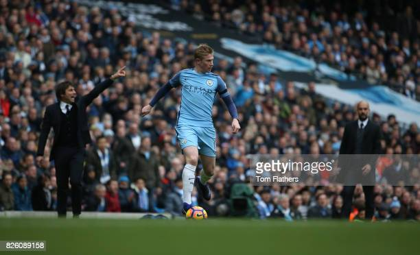 Manchester City's Kevin De Bruyne in action as Pep Guardiola and Antonio Conte look on