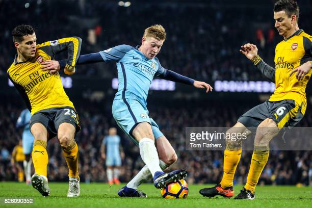 Manchester City's Kevin De Bruyne in action with Arsenal's Granit Xhaka and Laurent Koscielny