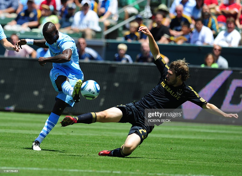 Manchester City's Micah Richards (L) shoots against Los Angeles Galaxy's Kyle Davies (R) at the World Football Challenge, at the Home Depot Center in Carson, California July 24, 2011. Manchester City defeated LA Galaxy 7-6 in a penalty-kick shootout after a 1-1 draw AFP PHOTO / Robyn Beck
