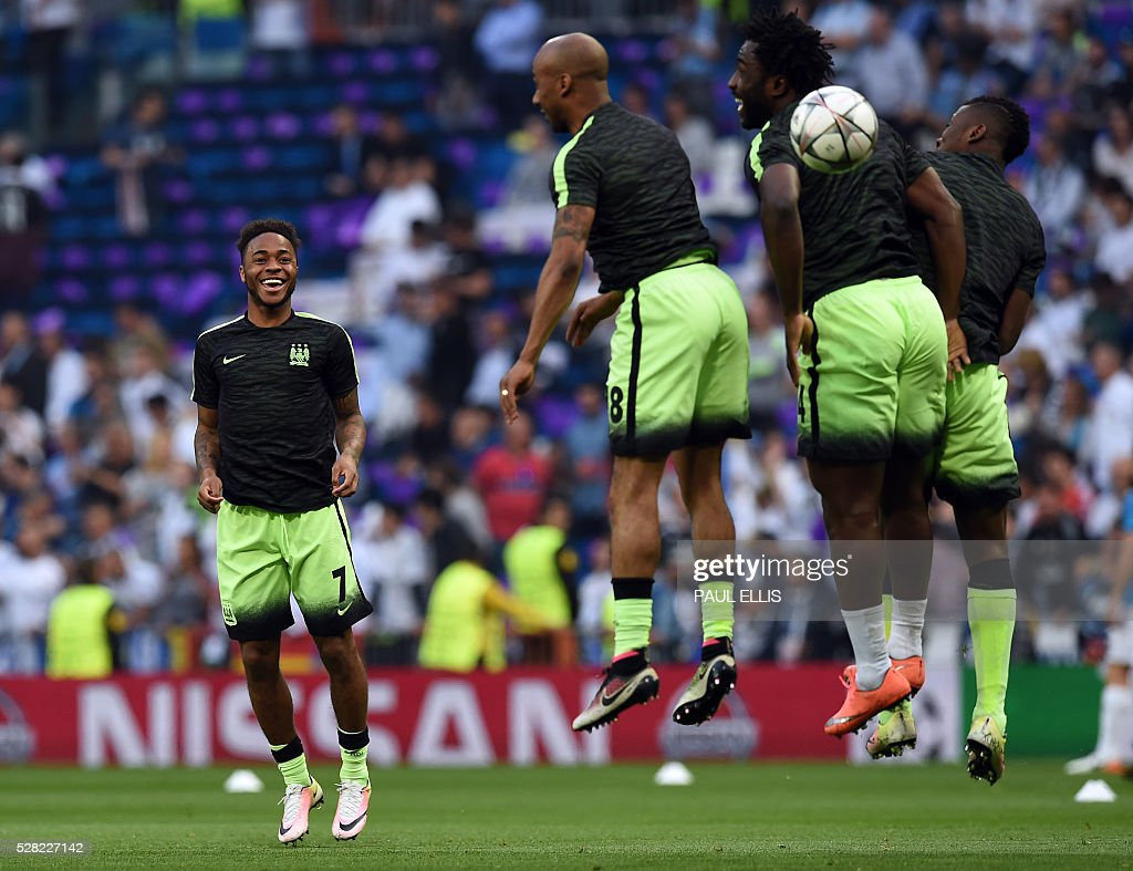 Manchester City's midfielder Raheem Sterling (L) smiles as he warms up with Manchester City's midfielder Fabian Delph (2nd L) and Manchester City's Ivorian forward Wilfried Bony (2nd R) before the UEFA Champions League semi-final second leg football match Real Madrid CF vs Manchester City FC at the Santiago Bernabeu stadium in Madrid, on May 4, 2016. / AFP / PAUL