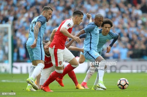 Manchester City's Nicolas Otamendi and Fernandinho battle for the ball with Arsenal's Granit Xhaka