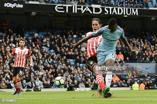 Manchester City's Nigerian striker Kelechi Iheanacho shoots to score their first goal under pressure from Southampton's Dutch defender Virgil van...