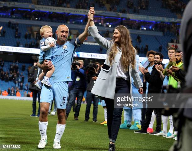 Manchester City's Pablo Zabaleta shows emotion as he walks off after the match alongside wife Christel Castano and son Asier