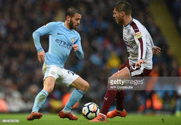 Manchester City's Portuguese midfielder Bernardo Silva vioes with Burnley's Irish midfielder Jeff Hendrick during the English Premier League football...