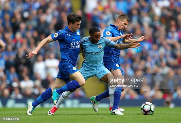 Manchester City's Raheem Sterling battles for the ball with Leicester City's Marc Albrighton and Ben Chilwell