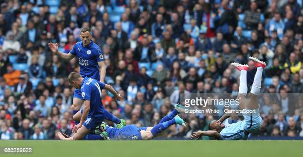 Manchester City's Raheem Sterling is dispossessed by Leicester City's Marc Albrighton and Ben Chilwell during the Premier League match between...